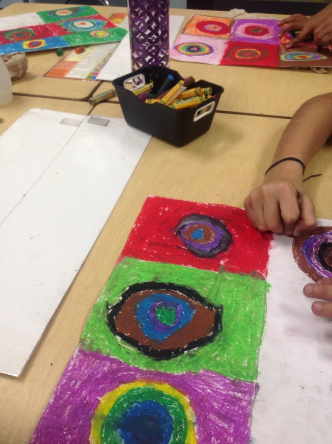 Students use Oil pastel, to create concentric circles influenced by the artist Kandinsky